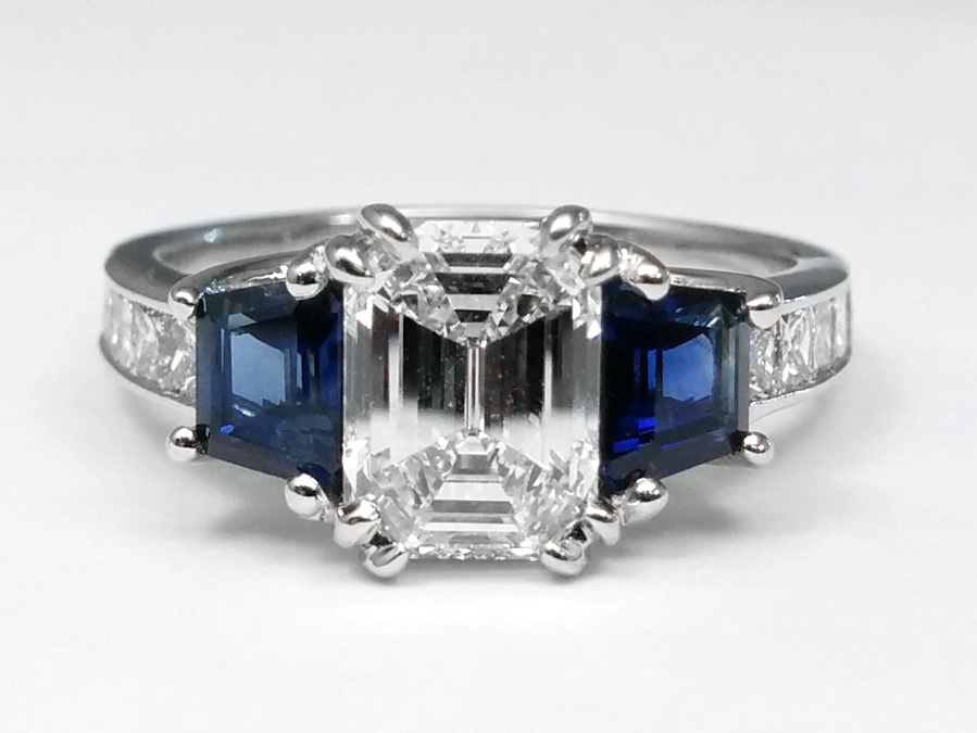 Emerald Cut Diamond With Princess Cut Diamonds & Trapezoid Cut Blue Sapphires in 14k White Gold